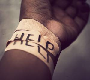 "A suicide wrist bandage with ""help"" written on it"