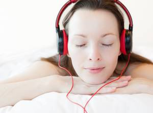 Woman with wired headset relaxing on bed