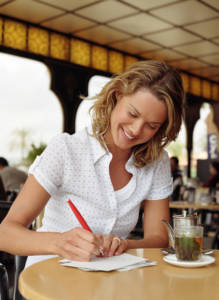 Young woman at table writing traditional mail by a teapot and glass, smiling