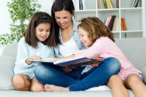 Mother with her daughters reading a book at home.