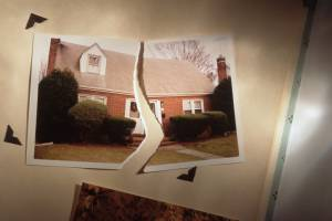 Torn photo of home symbolizes divorce