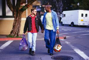 Gay couple walking through gay village carrying groceries