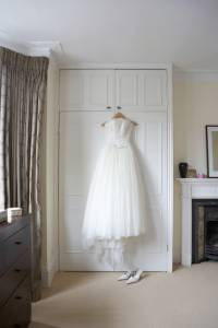 Bridal Gown hanging on closet door, white shoes on floor