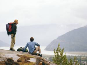 Hiking couple resting on rock overlooking town, rear view. date idea.