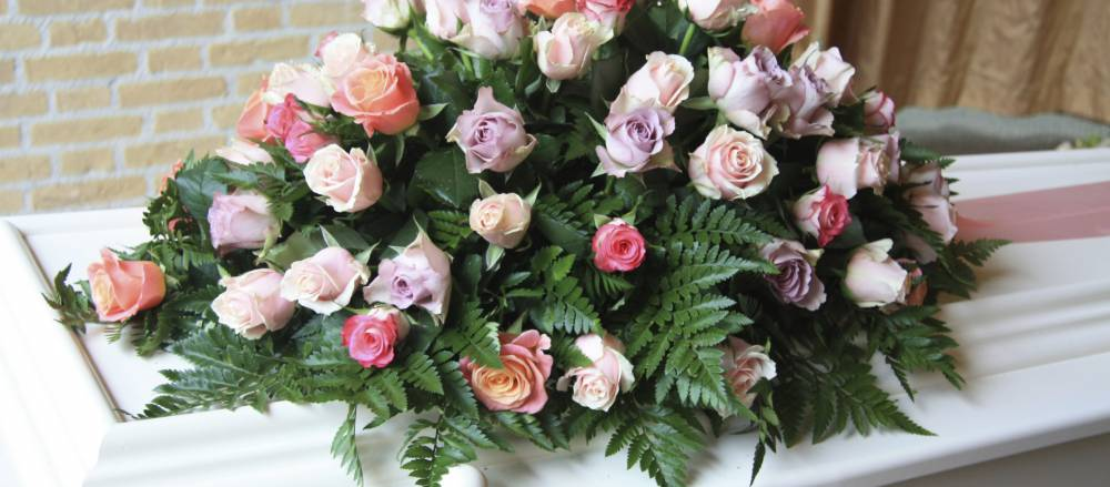 A casket adorned with a bouquet of flowers