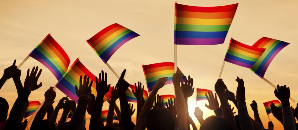 Supporters waving rainbow flags