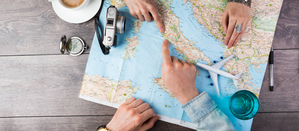 couple pointing at map, planning honeymoon